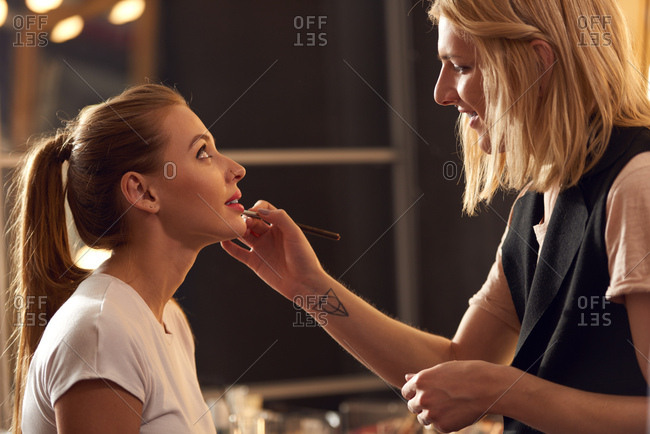 Transgender in makeup business. Concentrated androgynous make-up artist putting lipstick on lips of young beautiful female model in studio