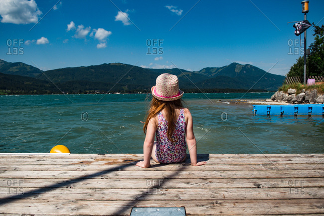 Girl sitting at a lake in the mountains in Austria