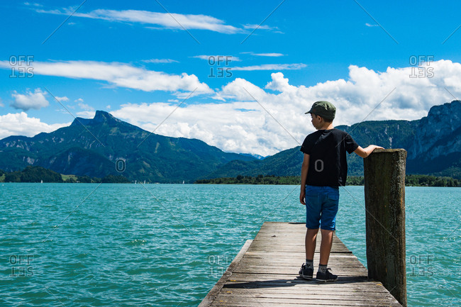 Boy looking at a lake in mountains in Austria