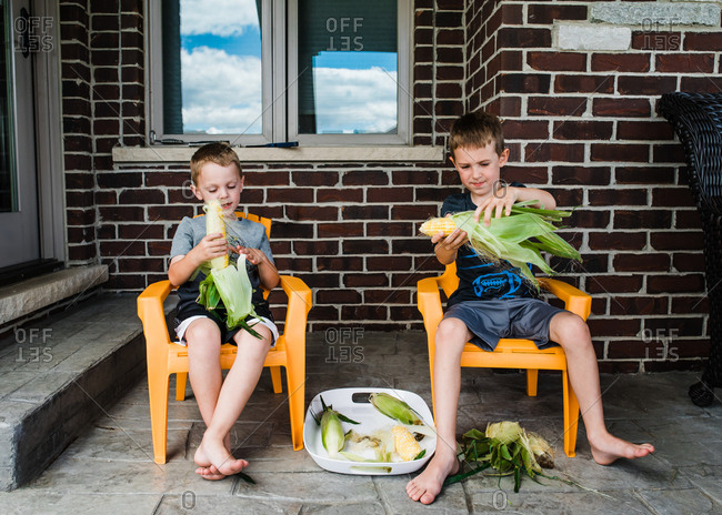 Two boys sitting on a porch shucking corn cobs