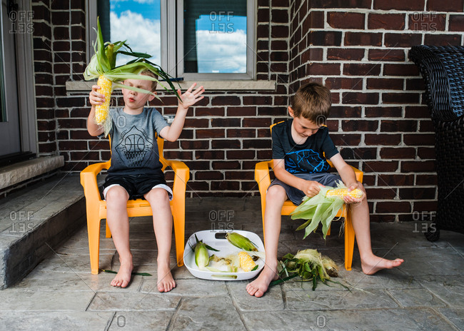 Two boys shucking corn on a porch