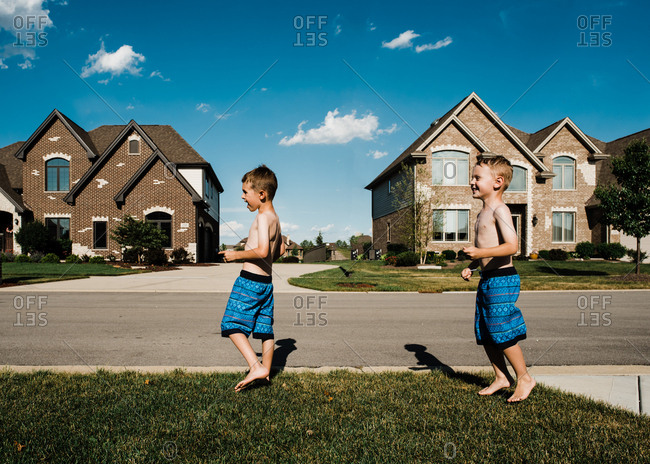 Two brothers playing on a lawn in swim trunks