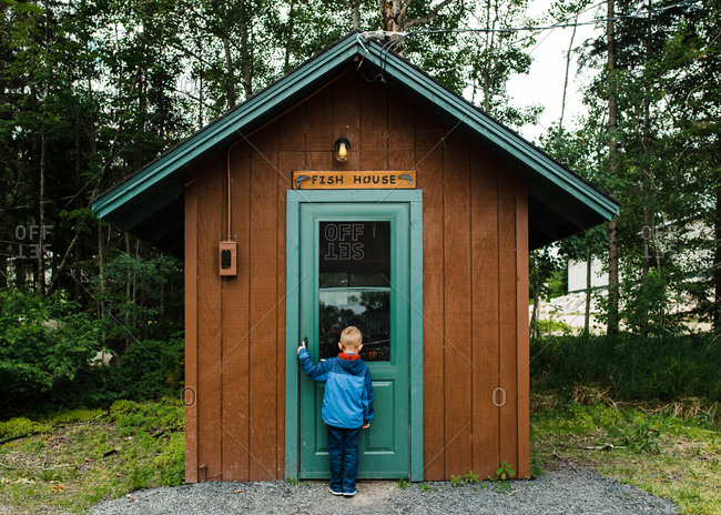 Boy standing at the entrance of a small fishing cabin
