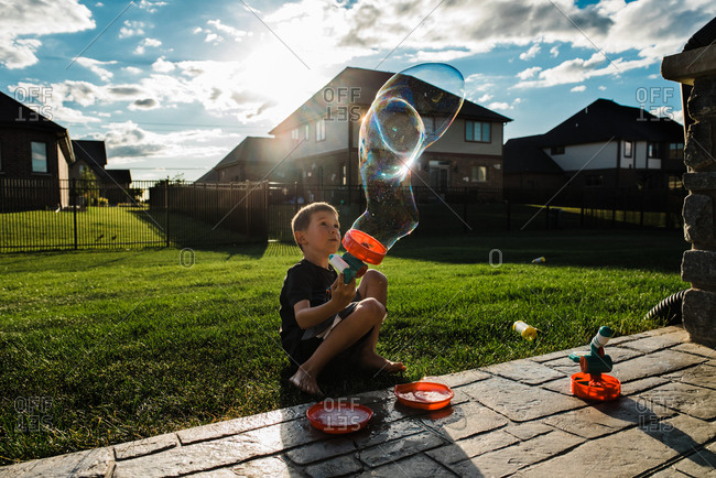 Boy playing with a bubble gun in a backyard