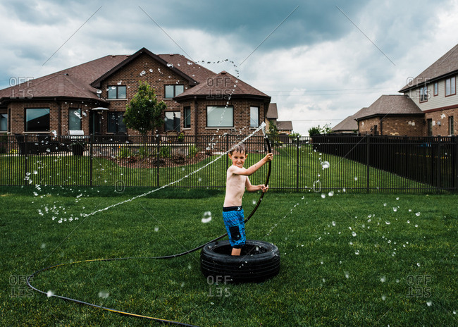 Little boy playing with a garden hose in a backyard