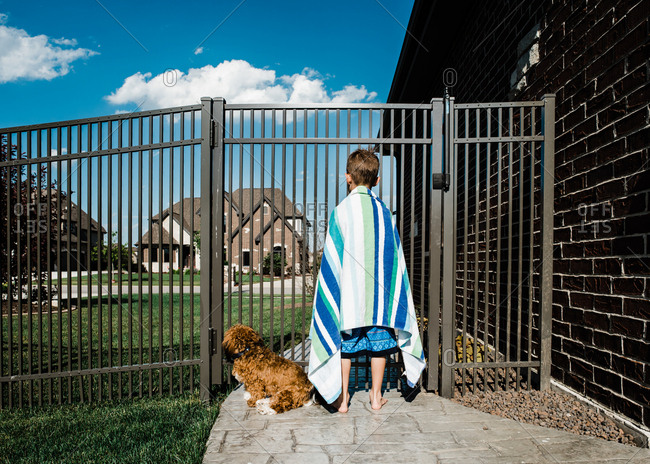 Little boy standing at a fence wrapped in a towel with his dog