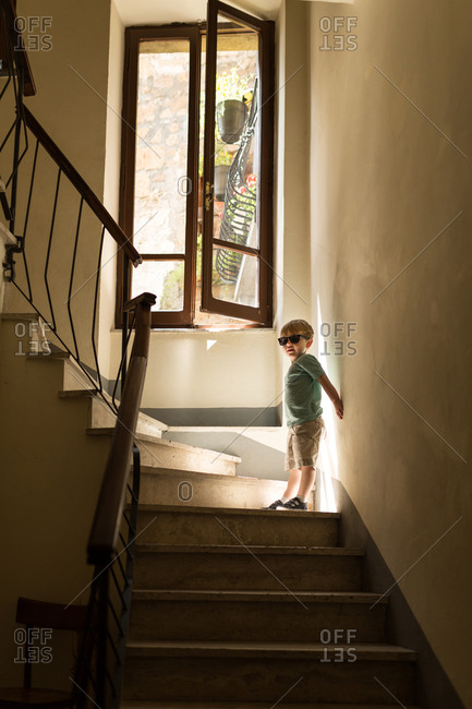 Boy in stairs under window