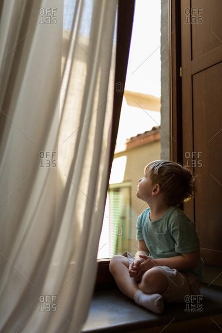 Boy sitting in window