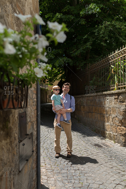 Father carrying son on cobblestone road