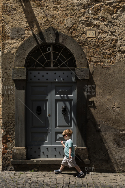 Boy walking in Europe by blue door