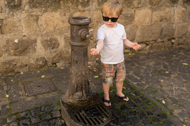 Young boy turning on water fountain