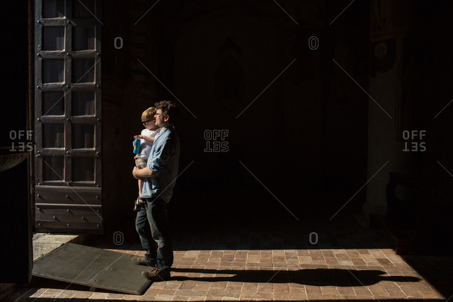 Father carrying son in doorway