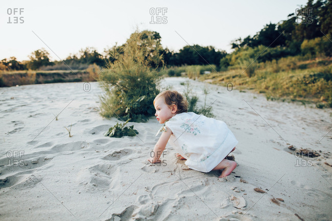 A little girl playing on a sandy river bed
