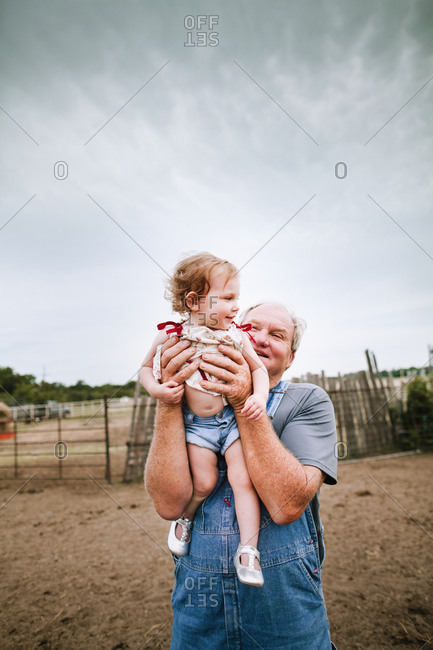 Grandfather holding little girl outside
