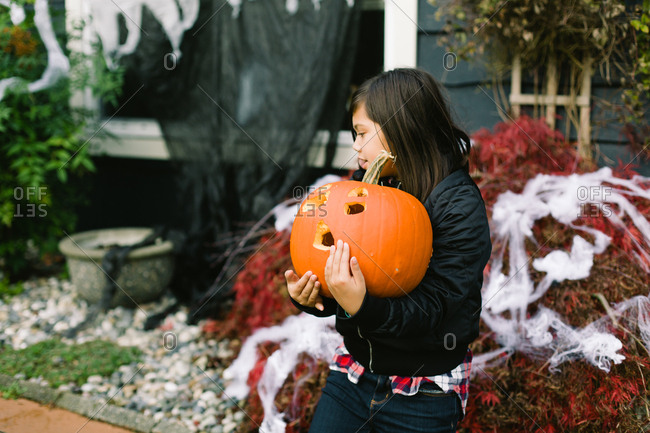Girl carrying carved pumpkin outside