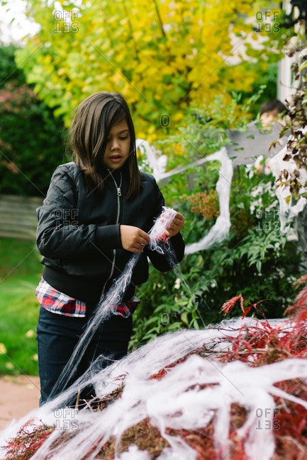 Girl decorating bushes with spider webs