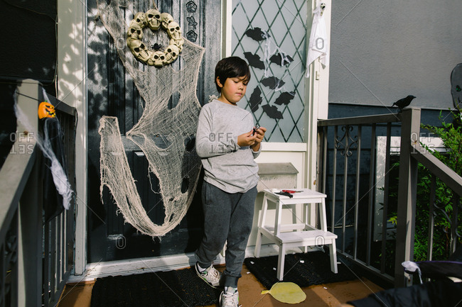 Boy decorating font porch for Halloween