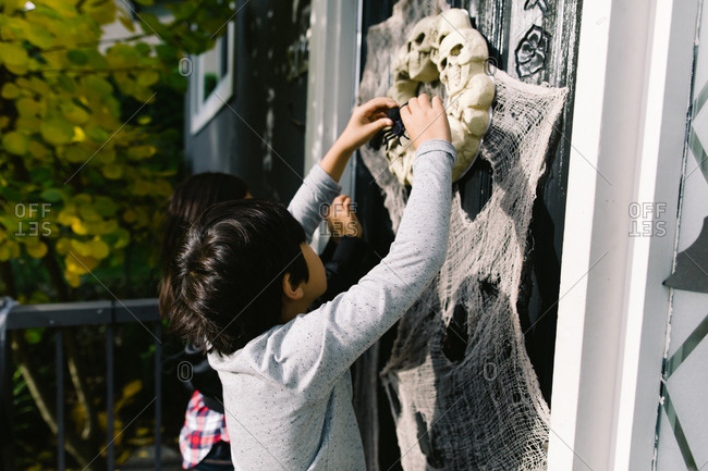 Children decorating front door for Halloween