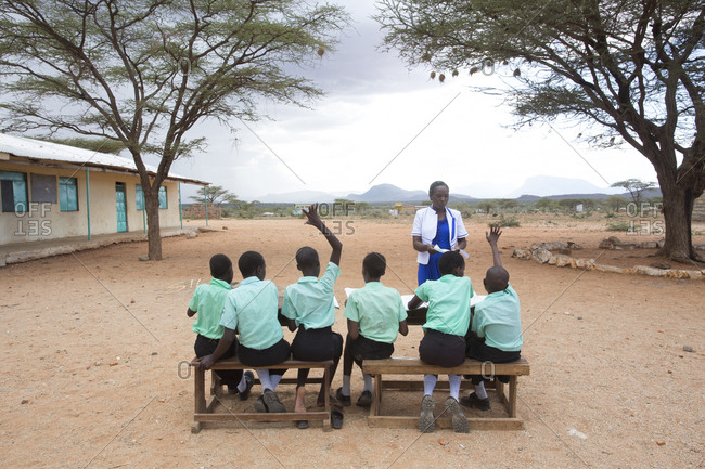 Isiolo, Samburu, Kenya - April 26, 2017: School teacher with school girls, teaching class outside at the Lorubae Primary School