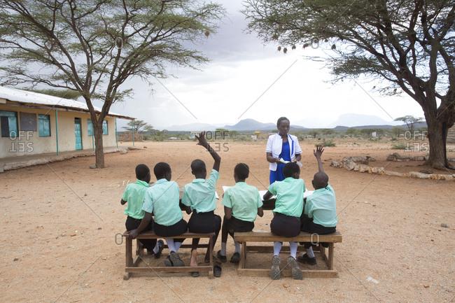 Isiolo, Samburu, Kenya - April 26, 2017: School teacher with school girls, teaching class outside at the Lorubae Primary School