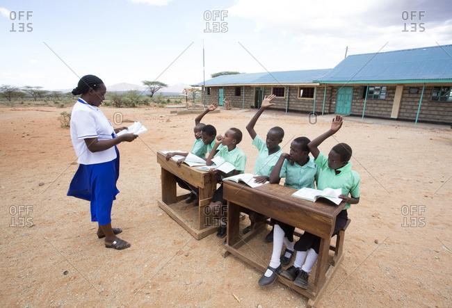 Isiolo, Samburu, Kenya - April 26, 2017: Teacher with school girls, giving lesson outdoors at the Lorubae Primary School