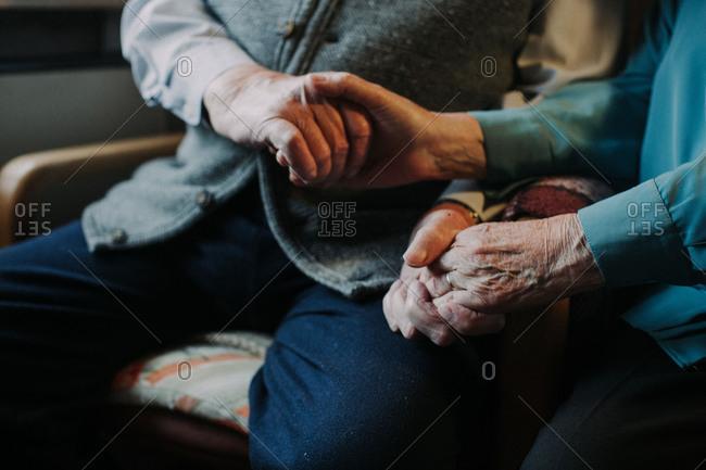 Senior couple holding hands, medium close-up, detail,