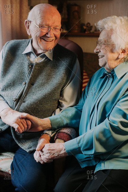 Senior couple holding hands, happy, laughing,