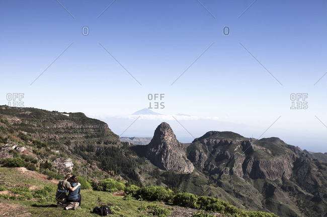 Hiker sits on a trunk at hiking trail 16 on La Gomera, El Tide / Tenerife in the background