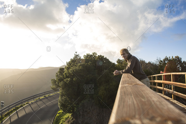 Man stands on bridge and enjoys the view