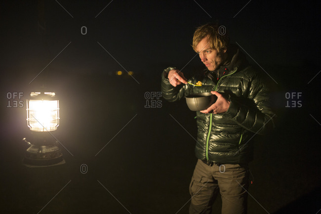 Man eats from mess kit and looks in a lantern