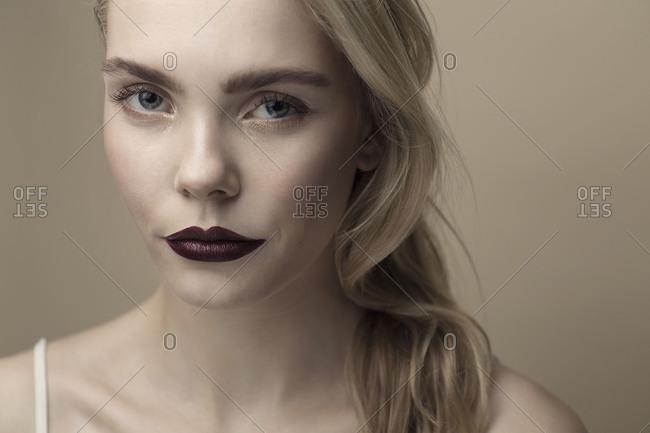 female model in front of beige studio background