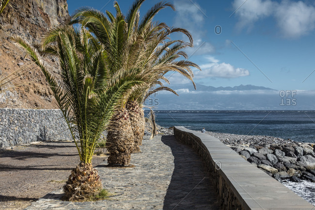 A way close to the harbor in San Sebastian de la Gomera with palm trees, view to Tenerife