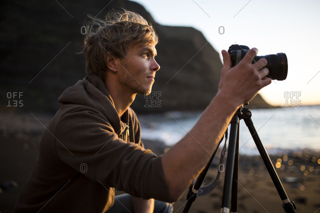Man on the beach while taking photos