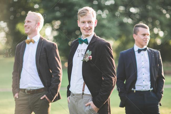 Bridegroom and groomsman outside, half portrait