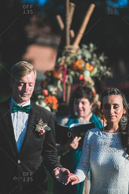 Alternate bridal couple at spiritual wedding ceremony outdoors, half portrait