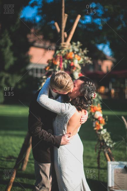 Alternate bridal couple outside, embrace, kiss
