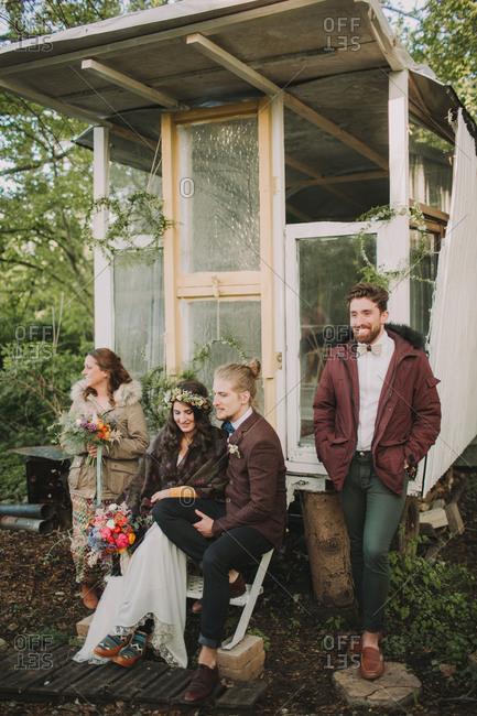 Bride and groom at alternative wedding before garden pavilion