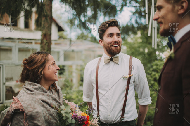 Alternative wedding, bride and groom in conversation with a friend