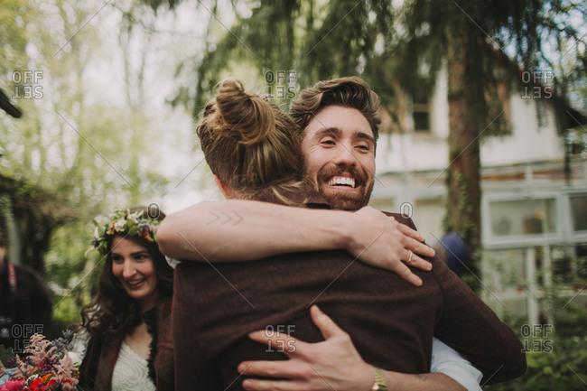Alternative wedding, Friend hugs the groom