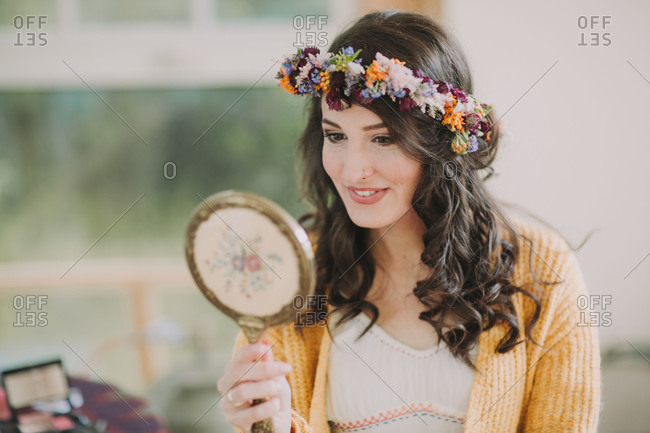 Alternative wedding, bride with floral wreath looks at herself in the mirror