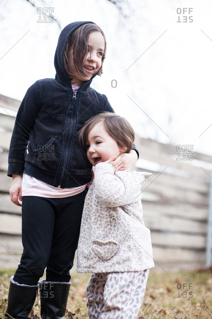 Girls hugging in front of a fence
