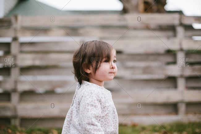 Little girl standing looking in a backyard
