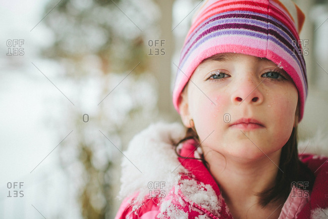 Girl in winter coat and hat with snow flakes on her eyelashes