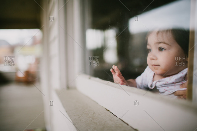 Girl looking out window on porch