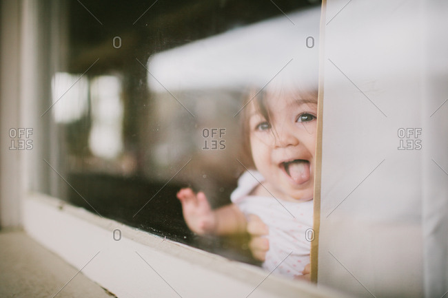 Cute female toddler looking out front porch window