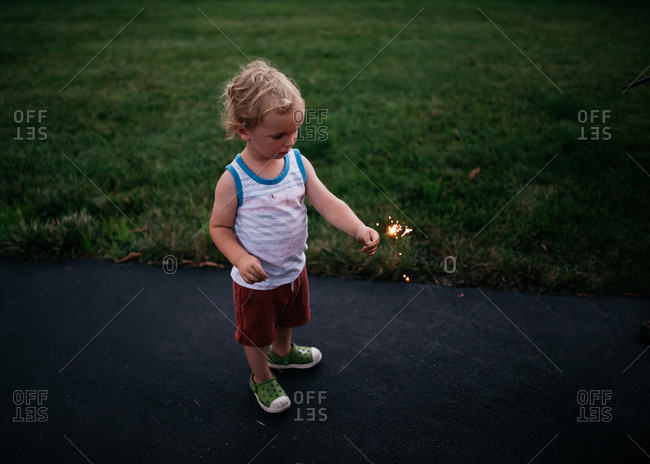 Little blonde boy holding lit sparkler