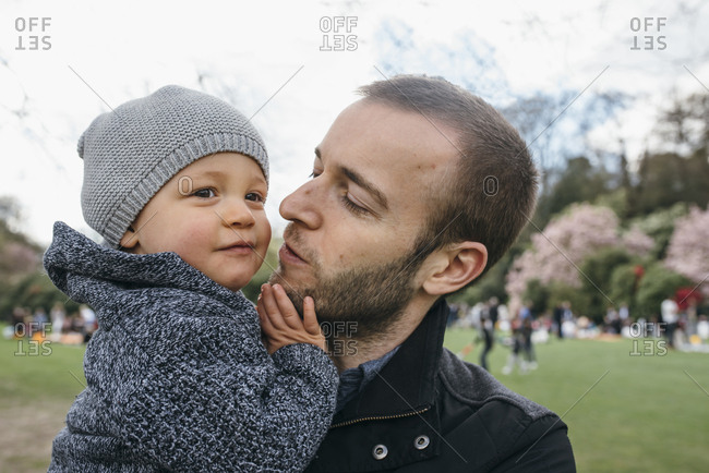 Father about to kiss his son at the park