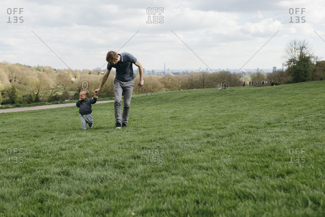 Father holding his son walking at the park