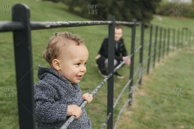 Young boy looking away while holding a fence