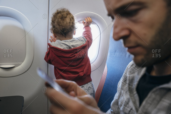 Young boy playing with window shade during flight